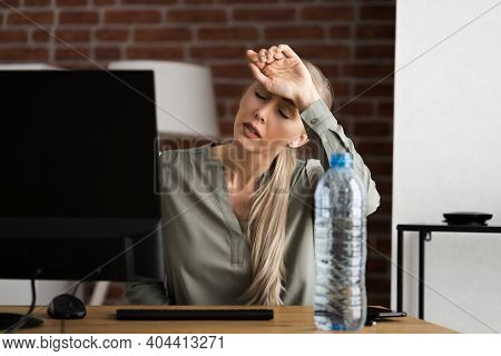 Thirsty Person Working At Desk With Bottle Of Water