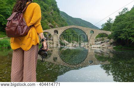 Fashion Backpacker Traveling In Bulgaria And Enjoying Devil Bridge. Lady Photographer Blogger Holdin