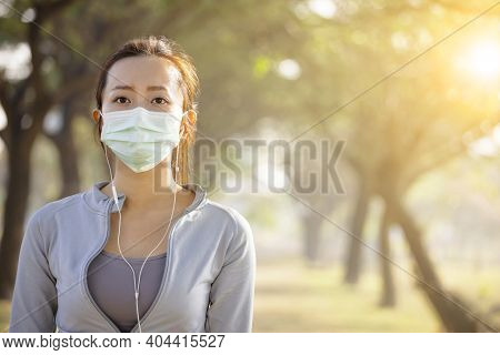 Young Woman In Face Mask And Ready Jogging In The Park