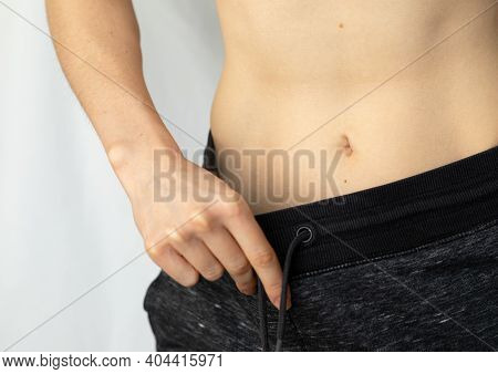Flat Female Belly. Woman Showing Her Flat Belly. Body Parts: Athletic Young Woman's Belly. Visible M