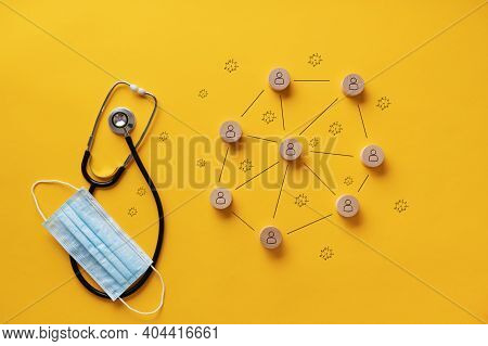 Spreading Of Covid19 Conceptual Image - Medical Stethoscope And Protective Mask Next To A Diagram Of