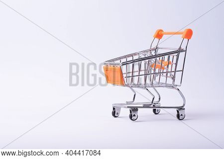 Small Toy Shopping Trolley On A White Background, Copy Space, Shopping Concept. Grocery Supermarket
