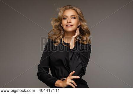 Posh Blonde Woman In Black In Studio.