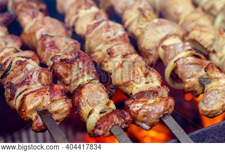 Shish Kebab Of Meat Skewered On A Grill Close-up Outdoors