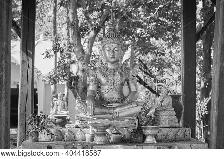 Phayao, Thailand - Dec 6, 2020: Black And White God Statue In Pavilion On Green Forest Background In