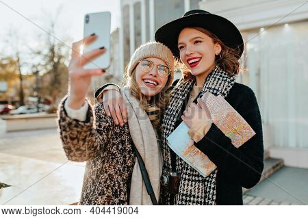 Adorable Woman In Black Hat Holding City Map. Outdoor Photo Of Good-humoured Girl Making Selfie Duri