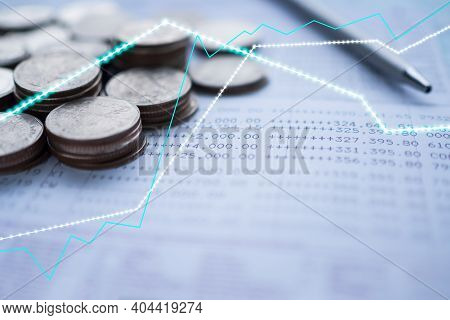 Plan Save Money 2021 Concept. Stock Charts On Blur Image Of Coins, Bankbook, Pen. For Stock Market A