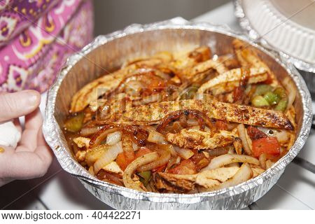 Woman Opening A Carryout Tin Of Stir Fried Chicken In A Serving Tin With Jalapenos, Roasted Green Be