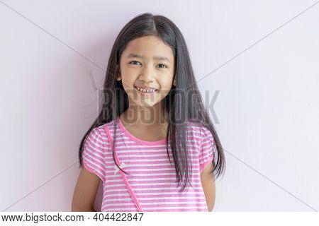 Asian Little Girl Smiling Brightly. Children Wearing Pink Cross White Dresses And Long Black Hair. T