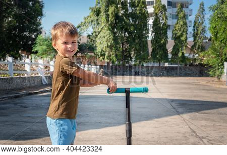 Portrait Of A Child With A Scooter Outside. The Boy Smiles And Holds A Scooter.