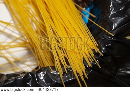 Large Quantity Of Uncooked Spaghetti Pasta Noodles In The Garbage Can