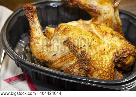 Whole Roasted Chicken In A Black Carryout Container Next To A Grey Napkin And Silverware
