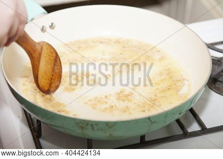 Stirring Minced Garlic Into Butter To Make A Sauce