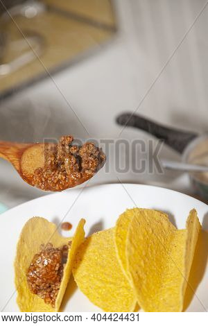 Woman Putting Cooked Ground Beef Into Corn Taco Shells With A Wooden Spoon