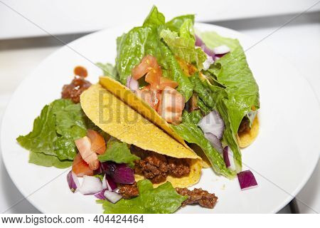 Three Ground Beef And Salad Tacos Made With Romaine Lettuce, Diced Tomato And Diced Purple Onion On