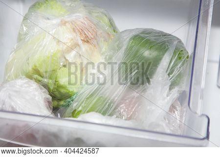 Head Of Iceberg Lettuce, Onion, Tomato, And Bell Peppers In Vegetable Bags In The Crisper Bin