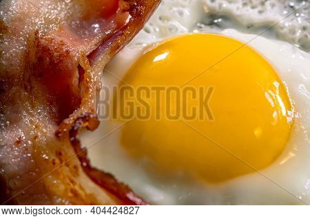 Fried Egg With Bacon In The Black Frying Pan. Selective Focus