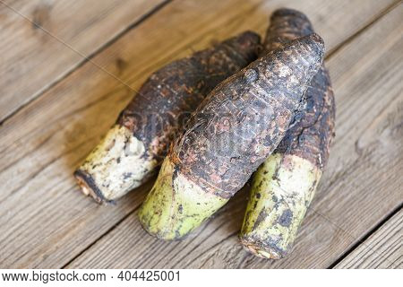 Taro Root Ready To Cook, Raw Organic Brown Taro On Wooden Table