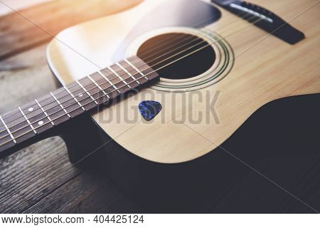 Guitar Resting On Old Wooden Background, Close Up Acoustic Guitar And Guitar Pick