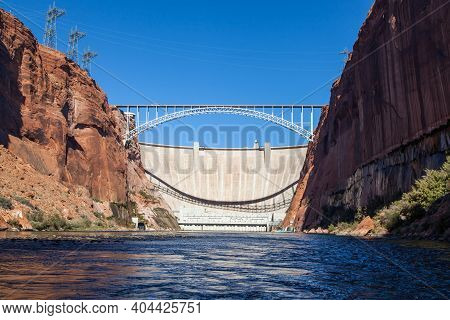 The Glen Canyon Dam Holding Back Lake Powell And The Glen Canyon Bridge With A Clear Blue Sky Backgr