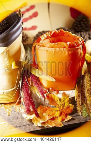 A Hunter Orange Pouch On A Wooden Slab Next To Orange And Red Berries And Leaves Between Boots With