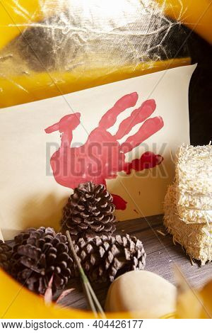 Red Hand Turkey On Vanilla Construction Paper With Hay And Pinecones, In A Yellow Frame, With A Gold