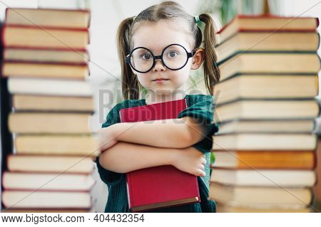 Preschool Age Girl In Big Round Glasses Holding Red Book Among Book Piles.