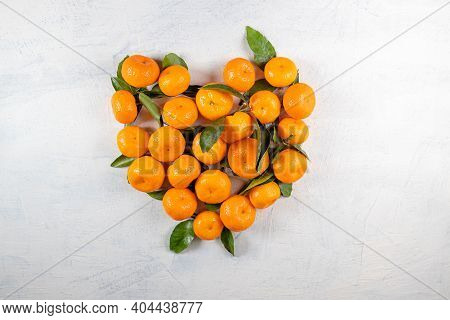 Orange Tangerines With Green Leaves In The Shape Of A Heart On A White Stone Background. Heart Made