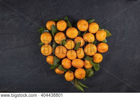 Orange Tangerines With Green Leaves In The Shape Of A Heart On A Black Stone Background. Heart Made
