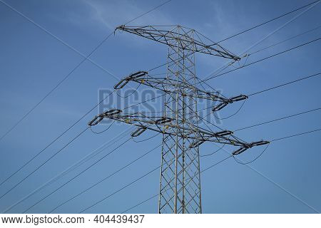 High Voltage Electrical Pylons With Wires Against The Sky. Electricity Pylon On A Blue Sky Backgroun
