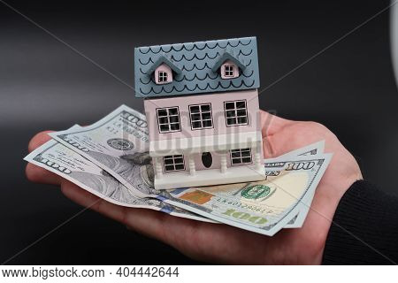 A Male Hand Holds A Toy House And One Hundred Dollar Dollar Bills, A Mortgage, A Loan, A Purchase Of