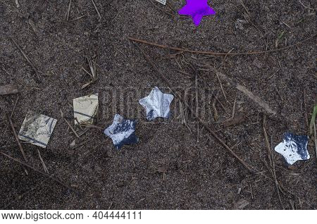 Glittery Holiday Tinsel In The Shape Of Stars On The Ground. Lilac And Purple Confetti Among The San