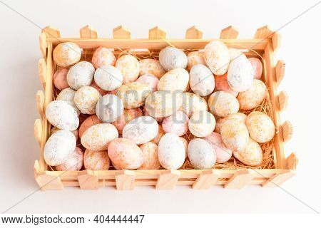 Mixed Chocolate Coated Easter Eggs Candies In A Small Squared Wooden Basket Isolated On A White Tabl