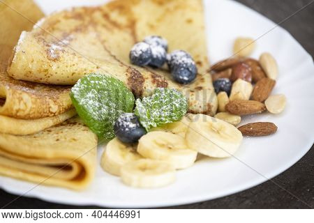 Pancakes With Nuts, Blueberries, Banana And Mint Leaves. Close-up On A Served Plate With Sweet Desse