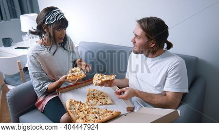Happy Young Multi Racial Couple Eating Pizza And Relaxing On The Couch. Slow Motion. High Quality Ph