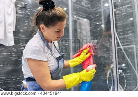 Cleaning Lady In Apron Gloves With Detergent Washing Glass Of Shower Cabin In Bathroom, House Cleani