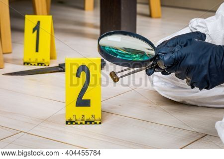 A Shell Casing Or Bullet At A Crime Scene With Evidence Markers