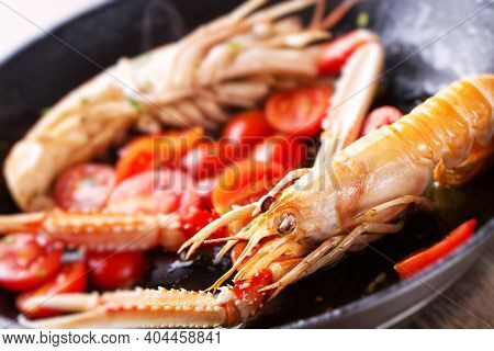 Scampi, Preparation And Cooking In A Pan. Shellfish Scampi Cooked In A Pan With Cherry Tomatoes
