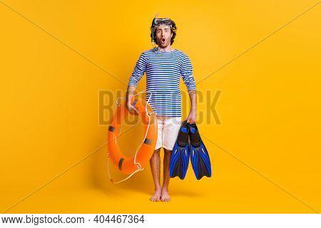 Full Length Photo Of Amazed Barefoot Guy Hold Life Buoy Flippers Wear Scuba Mask Goggles Isolated On