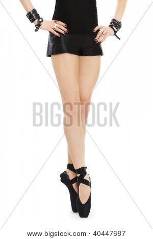 Beautiful legs of fit sexy woman in black leather shorts and ballet shoes, over white background