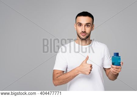 Brunette Hispanic Man Showing Thumb Up While Holding Toilette Water Isolated On Grey
