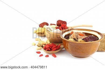 Close Up Of Chinese Herbs Clear Soup And Many Herbs On White Background