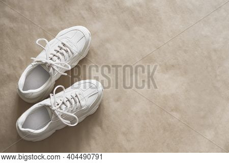 A Pair Of Light-colored Sneakers On Craft Wrapping Paper. Minimalistic Shoe Background, Fashion Blog