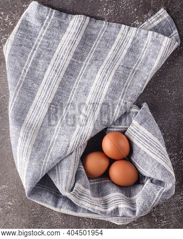 Chicken Eggs On A Textile Background. Eggs On Gray-blue Towel Background