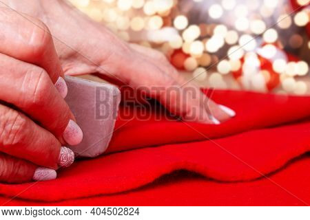 Grandma Sewing Small Santa Hat For Grandchildren. Close Up. Tailors Chalk In Hands To Make Sewing Pa