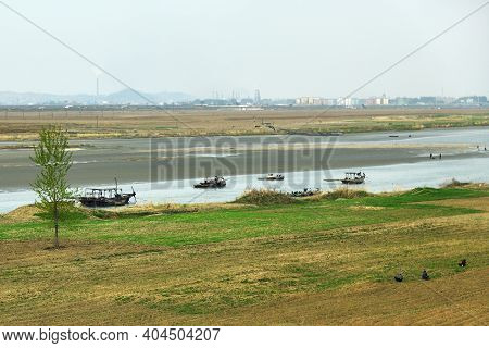View On The Taedong River At Dawn. Industrial Landscape On Background. North Korea