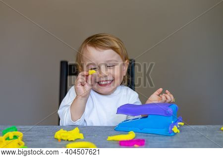Smiling Little Boy Moulds From Colored Plasticine On Table. Home Schooling. Creative Leisure With Ch