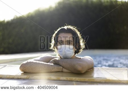 Young Man With Medical Protective Mask Leaning At The Poolside During Summer 2021, After Coronavirus