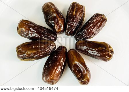 Date. Dried Dates On A White Background. Sweet Fragrant Delicious Brown Shiny Dates. Dried Fruits