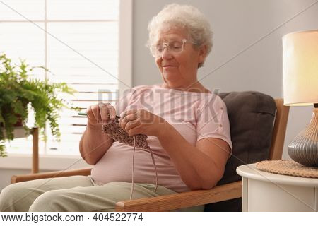 Elderly Woman Crocheting At Home. Creative Hobby